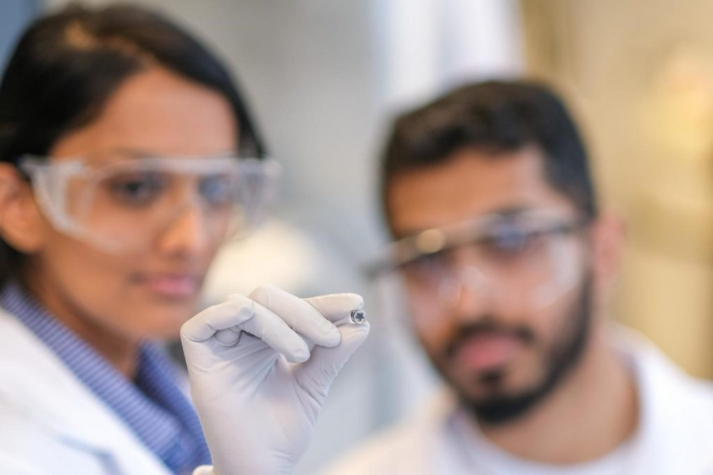 two researchers holding a pill sized device in tweezers