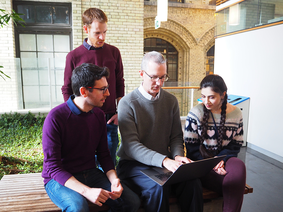 Four researchers looking at the data